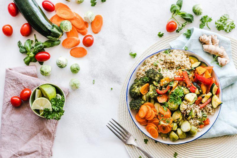 gerecht met wortels komkommers bruine rijst in ronde schaal met vork